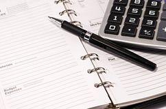 Cuaderno de notas con la pluma y la calculadora Foto de archivo