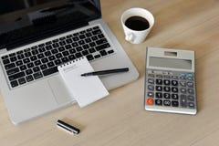 Cuaderno de notas en blanco, calculadora, ordenador, pluma en la tabla Imágenes de archivo libres de regalías