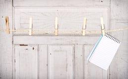 Cuaderno de notas que cuelga de una línea de ropa foto de archivo libre de regalías