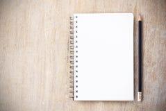 Cuaderno de notas y lápiz en la opinión de sobremesa de madera Imagen de archivo libre de regalías