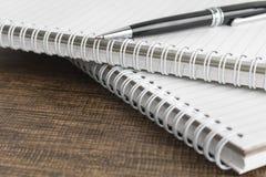 Cuaderno de notas y pluma en la tabla de madera Fotografía de archivo libre de regalías