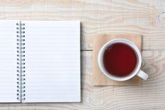 Cuaderno de notas y taza de té Imagenes de archivo