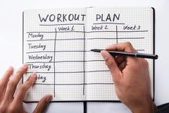 Cuaderno de Person Filling Workout Plan In foto de archivo
