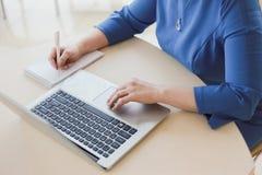 Cuaderno de trabajo de la escritura del ordenador portátil de la oficina de la mujer fotografía de archivo libre de regalías