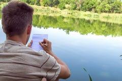 Cuaderno de un hombre joven, hombre cerca del lago, paisaje de pintura en libreta Día asoleado del verano Foto de archivo libre de regalías