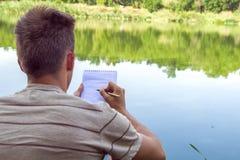 Cuaderno de un hombre joven, hombre cerca del lago, paisaje de pintura en libreta Día asoleado del verano Foto de archivo