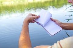 Cuaderno de un hombre joven, hombre cerca del lago, paisaje de pintura en libreta Día asoleado del verano para dar vuelta a la pá Foto de archivo libre de regalías