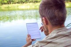 Cuaderno de un hombre joven, pluma, lápiz, hombre cerca del lago, paisaje de pintura en libreta Día asoleado del verano Imagenes de archivo