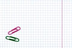 Cuaderno del estudiante en una jaula con una línea roja En la hoja son dos clips de papel verdes y púrpuras imágenes de archivo libres de regalías