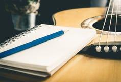 Cuaderno del lápiz en la guitarra acústica para el compositor Foto de archivo libre de regalías