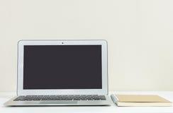 Cuaderno del ordenador del primer en la pared de madera blanca borrosa del escritorio y del papel pintado del color crema en el f Imagen de archivo