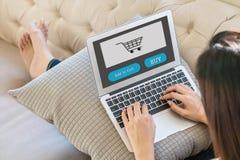 Cuaderno del ordenador del primer en el sofá con la mujer asiática que se sienta para hacer compras en línea en la forma de vida  Fotografía de archivo