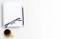 Cuaderno del papel en blanco y taza de café en el fondo blanco de la tabla Fotografía de archivo libre de regalías