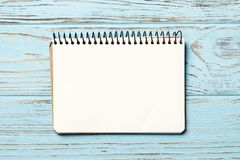 cuaderno del papel en fondo de madera azul imagenes de archivo