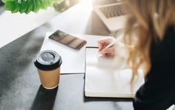 Cuaderno del primer en la tabla, pluma en mano femenina La muchacha está haciendo una nota en un cuaderno Aprendizaje del estudia foto de archivo