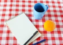 Cuaderno del vintage con una taza y una fruta en la tabla que espera Imagen de archivo
