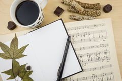 Cuaderno en blanco abierto con la taza de café y de libro de la notación de música, en la mesa de madera Imagen de archivo