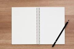 Cuaderno en blanco abierto del atascamiento espiral del anillo con un lápiz en superficie de madera Imagen de archivo libre de regalías
