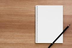 Cuaderno en blanco abierto del atascamiento espiral del anillo con un lápiz en superficie de madera Fotos de archivo