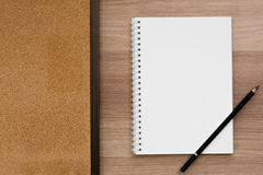 Cuaderno en blanco abierto del atascamiento espiral del anillo con un tablero del lápiz y del corcho en superficie de madera Foto de archivo