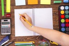 Cuaderno en blanco abierto, mano con un marco del brushwith del sorbo de la escuela Fotos de archivo libres de regalías