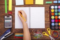 Cuaderno en blanco abierto, mano con un marco del brushwith del sorbo de la escuela Foto de archivo