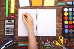 Cuaderno en blanco abierto, mano con un marco del brushwith del sorbo de la escuela Foto de archivo libre de regalías