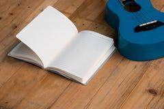 Cuaderno en blanco con la guitarra del ukelele Foto de archivo