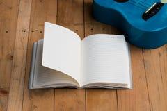 Cuaderno en blanco con la guitarra del ukelele Fotos de archivo libres de regalías