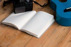 Cuaderno en blanco con la guitarra y la cámara del ukelele Fotografía de archivo libre de regalías