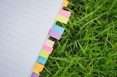 Cuaderno en blanco con la hierba del post-it del colorfull Foto de archivo libre de regalías
