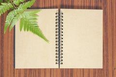 Cuaderno en blanco con la hoja del helecho en la tabla de madera Foto de archivo libre de regalías