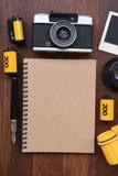 Cuaderno en blanco con la película de la foto, los marcos de la foto y la cámara Imágenes de archivo libres de regalías