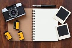 Cuaderno en blanco con la película de la foto, los marcos de la foto y la cámara Fotografía de archivo libre de regalías