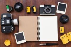 Cuaderno en blanco con la película de la foto, los marcos de la foto y la cámara Fotos de archivo