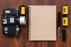 Cuaderno en blanco con la película de la foto, los marcos de la foto y la cámara Fotografía de archivo