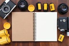 Cuaderno en blanco con la película de la foto y cámara en fondo de madera Foto de archivo libre de regalías