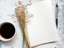 Cuaderno en blanco con la pluma al lado de una taza de café foto de archivo