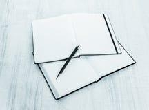 Cuaderno en blanco con la pluma en la madera Foto de archivo libre de regalías
