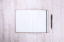 Cuaderno en blanco con la pluma en la madera Fotos de archivo libres de regalías