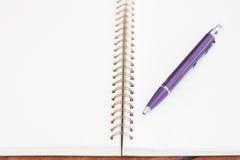 Cuaderno en blanco con la pluma en la tabla de madera Foto de archivo