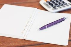 Cuaderno en blanco con la pluma en la tabla de madera Imagen de archivo libre de regalías