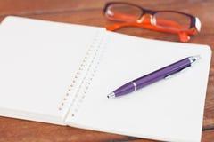 Cuaderno en blanco con la pluma en la tabla de madera Fotografía de archivo