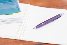 Cuaderno en blanco con la pluma en la tabla de madera Foto de archivo libre de regalías