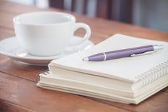 Cuaderno en blanco con la pluma en la tabla de madera Fotografía de archivo libre de regalías