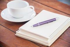 Cuaderno en blanco con la pluma en la tabla de madera Imágenes de archivo libres de regalías
