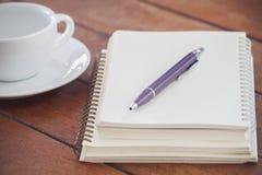 Cuaderno en blanco con la pluma en la tabla de madera Fotos de archivo