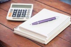 Cuaderno en blanco con la pluma en la tabla de madera Fotos de archivo libres de regalías