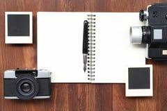 Cuaderno en blanco con la pluma, los marcos de la foto y la cámara Fotografía de archivo libre de regalías
