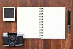 Cuaderno en blanco con la pluma, los marcos de la foto y la cámara Foto de archivo libre de regalías